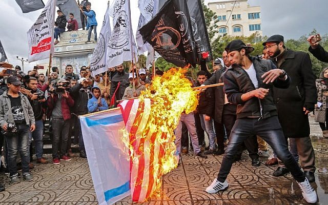 Palestinian protesters burn the US and Israeli flags in Gaza City on December 6, 2017, ahead of US President Donald Trump's speech regarding Jerusalem. (AFP PHOTO / MAHMUD HAMS)