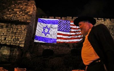 A picture taken on December 6, 2017, shows a giant US flag screened alongside Israel's national flag by the Jerusalem municipality on the walls of the Old City. (AFP PHOTO / Ahmad GHARABLI)