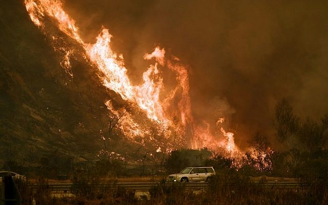 Vehicles pass beside a wall of flames on the 101 highway as it reaches the coast during the Thomas wildfire near Ventura, California on December 6, 2017. (AFP PHOTO / MARK RALSTON)