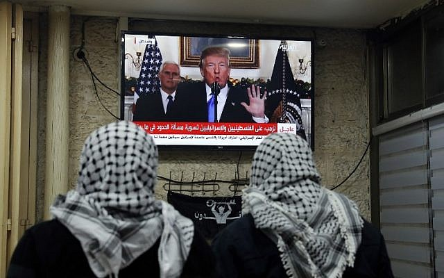 A picture taken on December 6, 2017 shows Palestinian men watching an address given by US President Donald Trump at a cafe in Jerusalem.  AFP PHOTO / Ahmad GHARABLI