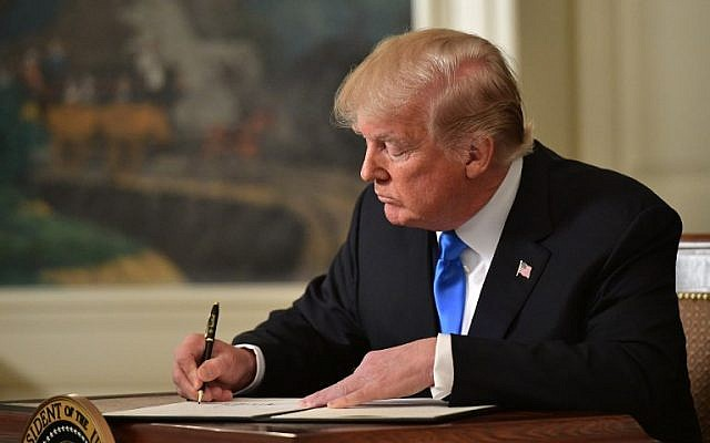 US President Donald Trump signs a memorandum after he delivered a statement on Jerusalem from the Diplomatic Reception Room of the White House in Washington, DC on December 6, 2017. (Saul Loeb/AFP)