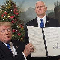 US President Donald Trump holds up a signed memorandum recognizing Jerusalem as Israel's capital, as US Vice President looks on, at the White House, on December 6, 2017. (AFP Photo/Saul Loeb)