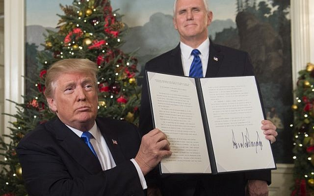US President Donald Trump holds up a signed memorandum after he delivered a statement on Jerusalem from the Diplomatic Reception Room of the White House in Washington, DC on December 6, 2017 as US Vice President Mike Pence looks on. (Saul Loeb/AFP)