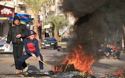 Palestinian youths set tires ablaze during a protest against US President Donald Trump's decision to recognize Jerusalem as the capital of Israel, in Gaza City, December 7, 2017. (MOHAMMED ABED/AFP)