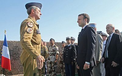 French President Emmanuel Macron (c)is welcomed by French Air Force commander Christophe Oursel (L) during his visit to French troops stationed at the al-Udeid Air Base in the Qatari capital Doha on December 7, 2017.  / AFP PHOTO / KARIM JAAFAR