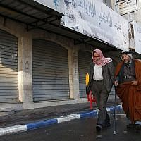 Illustrative: Palestinian men walk past closed shops in the West Bank city of Hebron as a general strike was called following US President Donald Trump's decision to recognize Jerusalem as the capital of Israel, December 7, 2017. (HAZEM BADER/AFP)