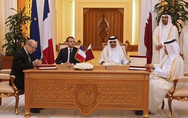 French President Emmanuel Macron (C-L), Qatari Emir Sheikh Tamim bin Hamad al-Thani (C-R) watch French Foreign Minister Jean-Yves Le Drian and his Qatari counterpart  Mohammed bin Abdulrahman al-Thani (R) sign bilateral agreements in the Qatari capital Doha on December 7, 2017.  (AFP/Karim Jaafar)