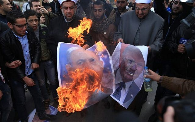 Palestinian protesters burn pictures of US President Donald Trump and Prime Minister Benjamin Netanyahu in Gaza City, on December 7, 2017. (AFP Photo/Mohammed Abed)