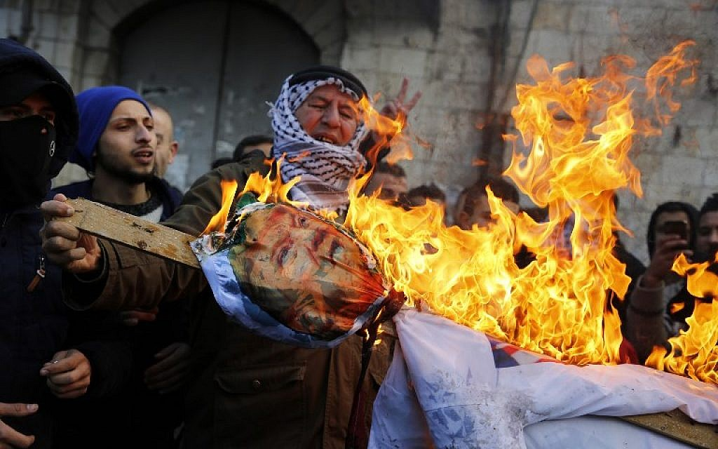 Palestinian protesters burn an effigy of US President Donald Trump following his decision to recognize Jerusalem as the capital of Israel, in the West Bank city of Nablus, on December 7, 2017.  (AFP PHOTO / Jaafar ASHTIYEH)