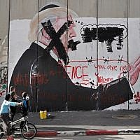 Palestinian children look at graffiti depicting US President Donald Trump and slogans against US Vice President Mike Pence painted on Israel's security barrier in the West Bank city of Bethlehem during clashes with Palestinian protesters near an Israeli checkpoint on December 7, 2017. (AFP/Thomas Coex)