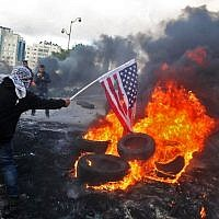 A Palestinian protester sets alight an America flag during clashes with Israeli troops at a protest against US President Donald Trump's decision to recognize Jerusalem as the capital of Israel, near the West Bank city of Ramallah on December 7, 2017.  (AFP PHOTO / ABBAS MOMANI/File)