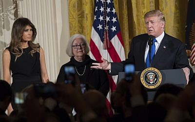 US President Donald Trump speaks alongside First Lady Melania Trump (L), and Holocaust survivor Louise Lawrence-Israels (C) during a Hanukkah reception in the East Room of the White House in Washington, DC, December 7, 2017. (AFP PHOTO / SAUL LOEB)