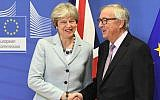 British Prime Minister Theresa May (L) is welcomed by European Commission Jean-Claude Juncker at European Commission in Brussels on December 8, 2017. (AFP PHOTO / EMMANUEL DUNAND)
