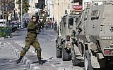An Israeli soldier throws a stun grenade toward Palestinian rioters during clashes in the West Bank city of Hebron on December 8, 2017. (Hazem Bader/AFP)