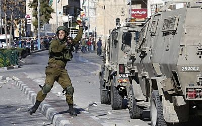 Illustrative. An Israeli soldier throws a stun grenade toward Palestinian rioters during clashes in the West Bank city of Hebron on December 8, 2017. (Hazem Bader/AFP)