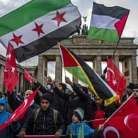 Demonstrators wave Palestinian, Turkish and Syrian flags in front of the Brandenburg Gate, next to the US embassy in Berlin on December 8, 2017, (AFP PHOTO / John MACDOUGALL)