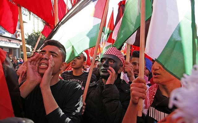 Palestinian youths protest with national flags near an Israeli checkpoint in the West Bank city of Ramallah on December 9, 2017, following the US president's recognition of Jerusalem as Israel's capital. (AFP/ ABBAS MOMANI)