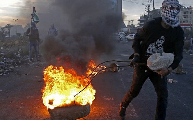 A Palestinian protester pulls a burning tire during clashes with Israeli security forces near an Israeli checkpoint in the West Bank city of Ramallah on December 9, 2017, following the US president's recognition of Jerusalem as Israel's capital. (AFP/Abbas Momani)