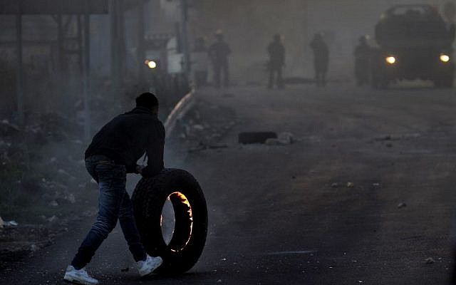 A Palestinian protestor pushes a burning tire towards Israeli security forces during clashes in the West Bank city of Nablus, on December 9, 2017, following a demonstration against US President Donald Trump's decision to recognize Jerusalem as the capital of Israel. (AFP PHOTO/ AAFAR ASHTIYEH)