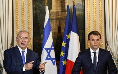 Israeli Prime Minister Benjamin Netanyahu speaks as French President Emmanuel Macron looks on during a joint news conference following their meeting at the Elysee Palace in Paris on December 10, 2017. (AFP PHOTO / POOL / PHILIPPE WOJAZER)