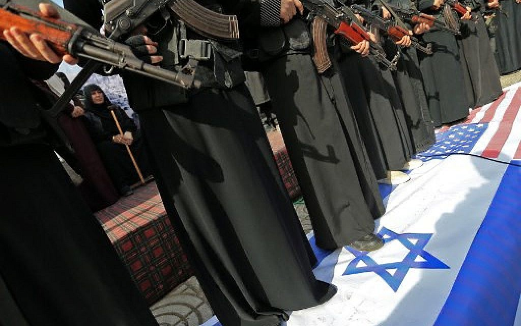 Armed female members of the Palestinian terrorist group Islamic Jihad carry Kalashnikov assault rifles while standing over banners depicting the Israeli and US flags, as they take part in a rally to protest against US President Donald Trump's decision to recognise Jerusalem as the capital of Israel, in Gaza City on December 11, 2017. (AFP PHOTO / MOHAMMED ABED)
