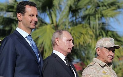 Syrian President Bashar al-Assad, left, Russian President Vladimir Putin, center, and Russian Defense Minister Sergei Shoigu inspect a military parade during their visit to the Russian air base in Hmeimim in the northwestern Syrian province of Latakia, December 11, 2017. (Mikhail Klimentyev/AFP)