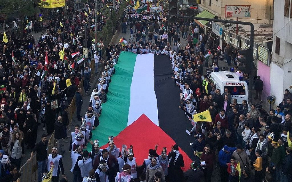A picture taken on December 11, 2017 shows demonstrators marching with a giant Palestinian flag as they wave flags of the Hezbollah terror group in a street in the Lebanese capital Beirut, protesting against the US president's recognition of Jerusalem as Israel's capital. (AFP Photo/Joseph Eid)