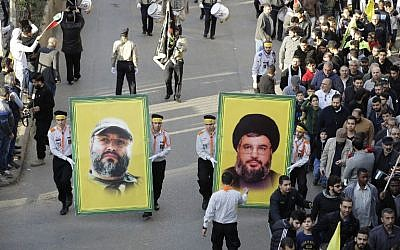 Supporters of Lebanon's Hezbollah terror group hold portraits of its leader Hassan Nasrallah (R) and its former military chief Imad Mughniyeh during a protest in Beirut on December 11, 2017; the story of Mughniyeh's targeted assassination by Israel is the subject of a new HBO/Keshet television series (AFP Photo/Joseph Eid)