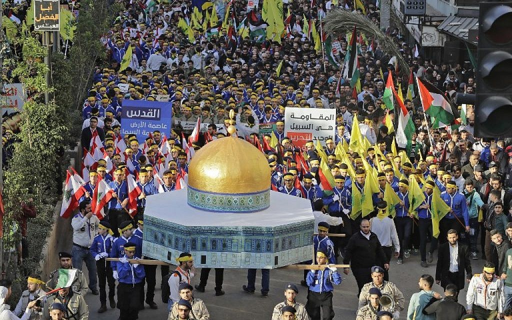 Supporters of Lebanon's Hezbollah terror group march with a model of the Dome of the Rock and wave Lebanese, Palestinian and Hezbollah flags during a protest in Beirut on December 11, 2017. (AFP Photo/Joseph Eid)