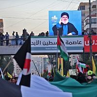 Hassan Nasrallah, the head of Lebanon's  Shiite terrorist movement Hezbollah, addresses the crowds through a giant screen at a rally agains US President Trump decision to relocate the US Embassy to Jerusalem, on December 11, 2017 in a Beirut southern suburb. (AFP PHOTO)