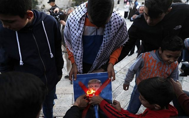 Palestinian youths set a portrait of US President Donald Trump on fire after his  recognition of Jerusalem as Israel's capital, during a demonstration outside Damascus Gate in Jerusalem's Old City on December 11, 2017.  (AFP/AHMAD GHARABLI)