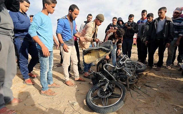Palestinians inspect the damaged remains of a motorcycle that exploded killing two Islamic Jihad members in Beit Lahia in northern Gaza Strip on December 12, 2017. (AFP PHOTO / MAHMUD HAMS)