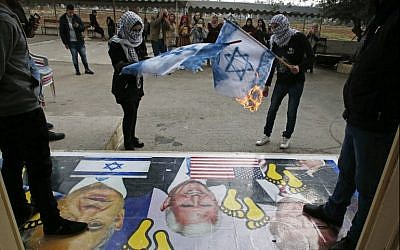 Palestinians burn Israeli flags next to a poster bearing images of US President Donald Trump (R), US Vice President Mike Pence (C), and Prime Minister Benjamin Netanyahu, during a demonstration at the al-Quds Open University in Dura, a village on the outskirts of the West Bank city of Hebron, on December 13, 2017.(AFP Photo/Hazem Bader)