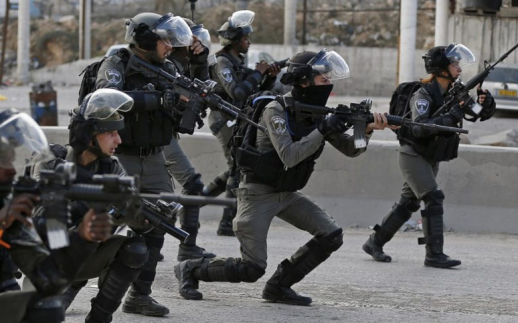 Illustrative: Border Police officers take aim at Palestinian rioters during clashes near the West Bank Qalandiya checkpoint, on the outskirts of Ramallah, on December 15, 2017. (Abbas Momani/AFP)