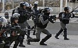 Border Police officers take aim at Palestinian rioters during clashes near the West Bank Qalandiya checkpoint, on the outskirts of Ramallah, on December 15, 2017. (Abbas Momani/AFP)