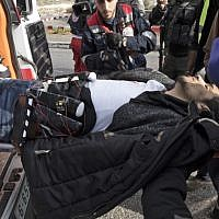 A Palestinian man, wearing a suspected suicide vest, is carried into an ambulance after he stabbed a soldier and was then shot  in the  West Bank town of al-Bireh on December 15, 2017. (Oren Ziv/AFP)