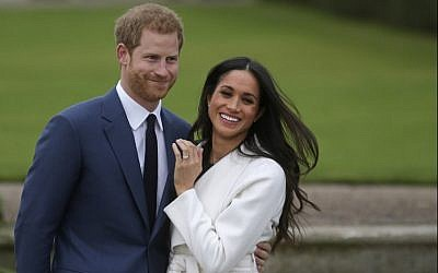 This file photo taken on November 27, 2017, shows Britain's Prince Harry standing with his fiancée US actress Meghan Markle as she shows off her engagement ring whilst they pose for a photograph in the Sunken Garden at Kensington Palace in London. (AFP Photo/Daniel Leal-Olivas)