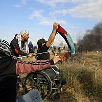 Wheelchair-bound Palestinian demonstrator Ibrahim Abu Thurayeh, waving a Palestinian flag during a protest along the Gaza-Israel border on December 15, 2017, as clashes with Israeli security forces against Washington's recognition of Jerusalem as Israel's capital intensified. (MOHAMMED ABED / AFP)