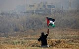 This  photo taken on May 19, 2017, shows handicapped Palestinian demonstrator Ibrahim Abu Thurayeh waving a Palestinian flag during clashes with Israeli soldiers following a protest against the blockade on Gaza, near the border fence east of Gaza City. (MOHAMMED ABED / AFP)