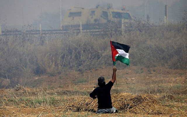 This  photo taken on May 19, 2017 shows handicapped Palestinian demonstrator Ibrahim Abu Thurayeh waving a Palestinian flag during clashes with Israeli soldiers following a protest against the blockade on Gaza, near the border fence east of Gaza City. (MOHAMMED ABED / AFP)