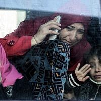 A Palestinian woman and child bid farewell through the window of a bus in Khan Younis in the southern Gaza strip on December 16, 2017 prior to their departure for the Rafah border crossing with Egypt. (AFP PHOTO / SAID KHATIB)