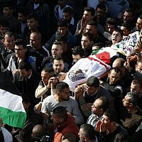 Mourners carry the body of Mohammed Aqal, a Palestinian assailant killed after carrying out a stabbing attack on a Border Police officer, during his funeral in the West Bank village of Beit Ula on December 16, 2017. (AFP Photo/ Hazem Bader)