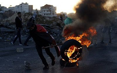 A Palestinian demonstrator moves a burning tire during clashes with Israeli forces near an Israeli checkpoint in the West Bank city of Ramallah on December 16, 2017l.  (AFP PHOTO / ABBAS MOMANI)