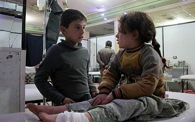 A Syrian boy talks to an injured girl as she lies on an operating bed in an emergency room in the rebel-held town of Douma in Syria's eastern Ghouta region, on December 17, 2017, following the reported shelling of the area by government forces. (AFP PHOTO / Hamza Al-Ajweh)