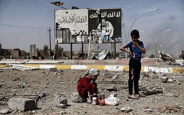 This file photo taken on March 12, 2017, shows Iraqi children sitting amidst the rubble of a street in Mosul's Nablus neighborhood in front of a billboard bearing the logo of the Islamic State terrir group. (AFP Photo/Aris Messinis)