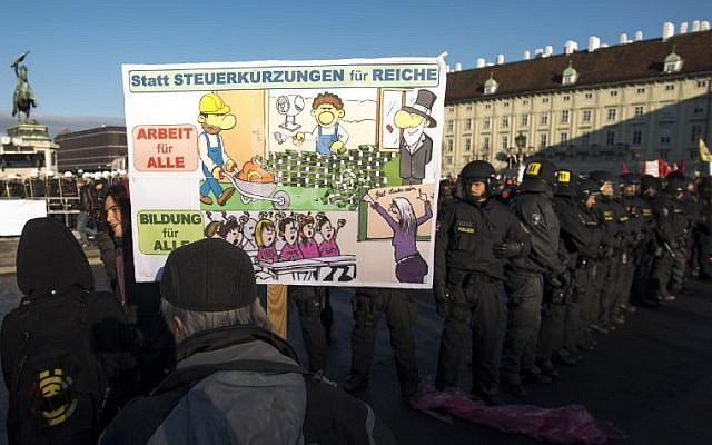 """A demonstrator with a banner reading """"Instead of tax cuts for the rich, work for all !"""" stands next to riot police during a protest against the new Austrian government near the presidential palace during the inauguration of the new Austrian government in Vienna, Austria, on December 18, 2017. ( AFP PHOTO / JOE KLAMAR)"""