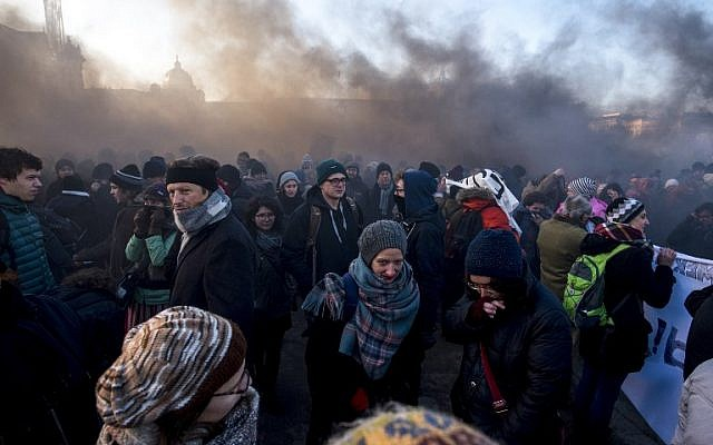 Demonstrators stand in the smoke rising from gas grenade during a protest against the new Austrian government near the presidential palace during the inauguration of the new Austrian government in Vienna, Austria, on December 18, 2017. ( AFP PHOTO / JOE KLAMAR)