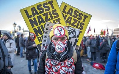 A protester stands with stickers depicting crossed out incoming vice-chancellor  of the far-right Freedom Party (FPOe) Christian Strache and incoming Austrian Chancellor of the conservative People's Party (OeVP) Sebastian Kurz during a protest near the presidential palace during the inauguration of the new Austrian government in Vienna, Austria, on December 18, 2017. (AFP PHOTO / JOE KLAMAR)