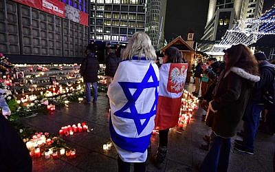 Women covered with Israeli (L) and Polish flags (R)  pay their respect at the memorial shift for the victims of the 2016 deadly truck attack at the Christmas market at Breitscheidplatz in front of the Kaiser-Wilhelm-Gedaechtniskirche during the commemorations marking one year after it occurred, on December 19, 2017 in Berlin. (AFP PHOTO / Tobias SCHWARZ)