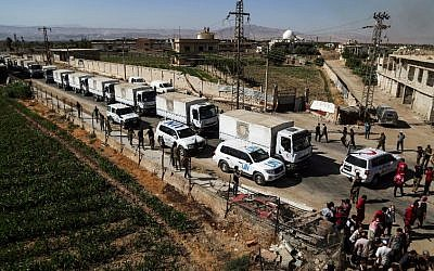 Illustrative: This photo taken on July 30, 2017 shows a United Nations and Syrian Arab Red Crescent convoy delivering aid packages in the rebel-held town of Nashabiyah in eastern Ghouta for the first time in five years. (AFP Photo/Amer Almohibany)